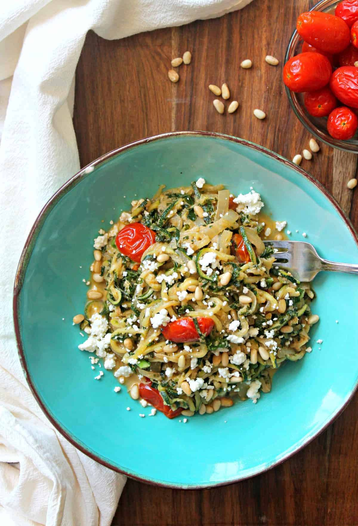 This tender zucchini pasta is sauteed and mixed with hearty kale, onions, and topped with goat cheese and roasted tomatoes