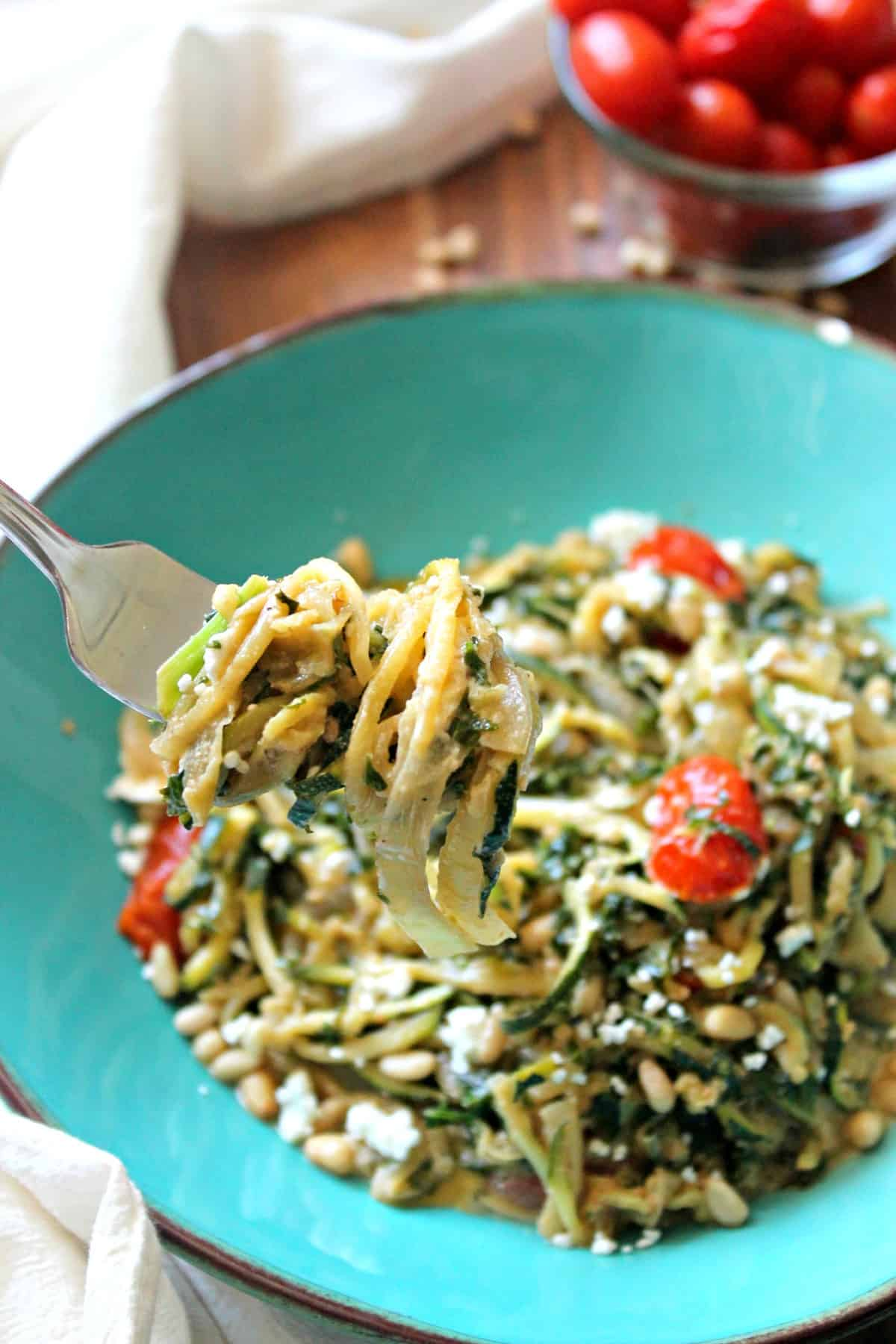 Creamy zucchini pasta with kale, onions, juicy roasted tomatoes, and creamy goat cheese