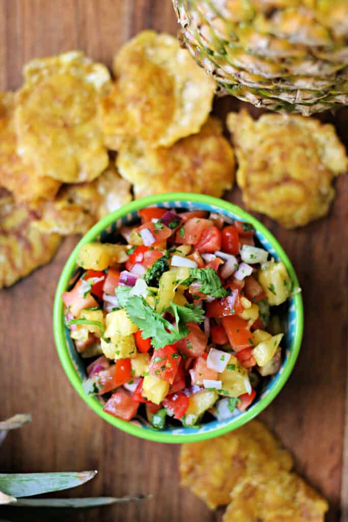 Pineapple Pico de Gallo salsa in a small bowl with plantain chips in the background.