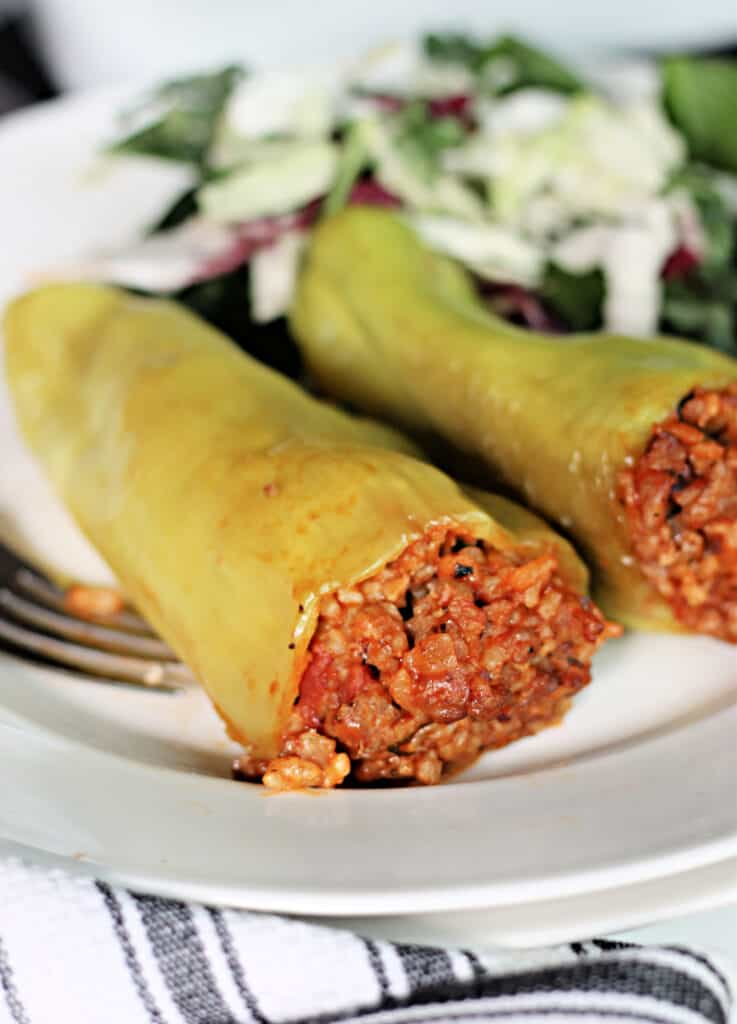 Two stuffed Cubanelle peppers on a plate.