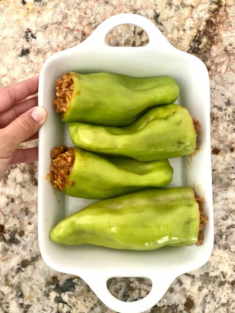 Four Stuffed Cubanelle Peppers in a white baking dish.