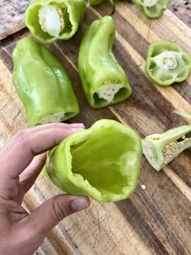 Showing the inside of a prepped Cubanelle pepper. Seeds and disgarded parts on a wooden cutting board below.