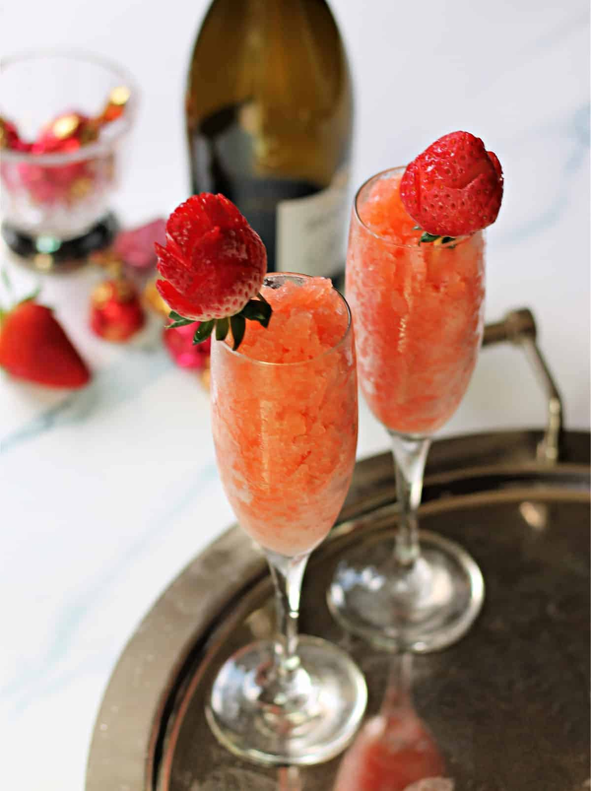 Two Strawberry & Champagne Granitas in champagne flutes on a silver serving tray.