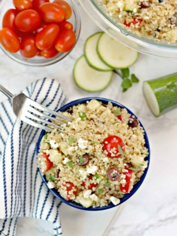Overhead shot of Mediterranean Quinoa Salad with fork, sliced zucchini and grape tomatoes in bowl.
