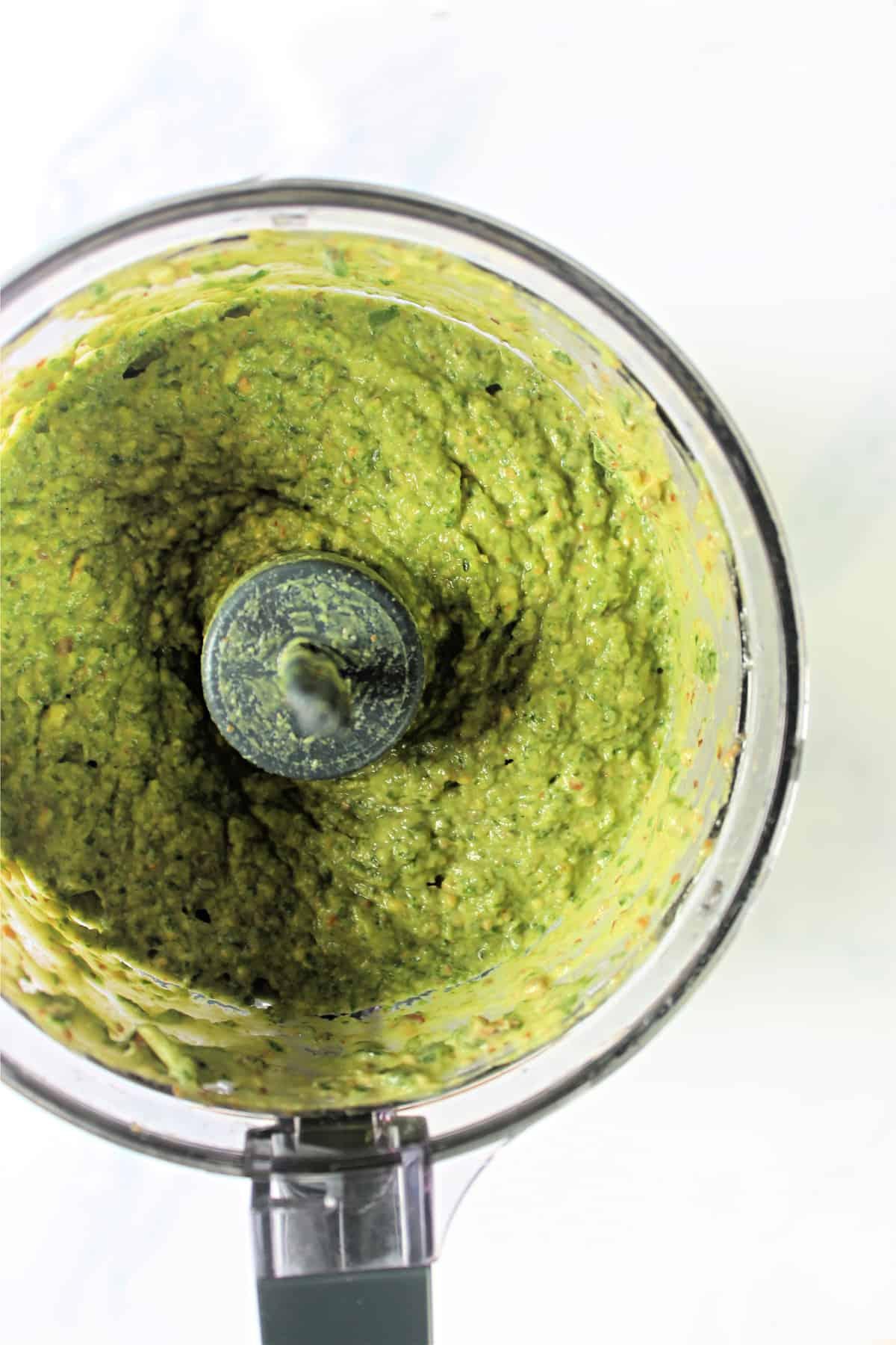 Overhead shot of avocado pesto in bowl of food processor.