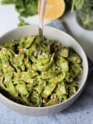 Close up of avocado pasta in a bowl with a fork in the center.
