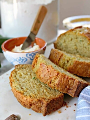 Close up shot of sliced Zucchini Bread with butter in a small bowl in background.