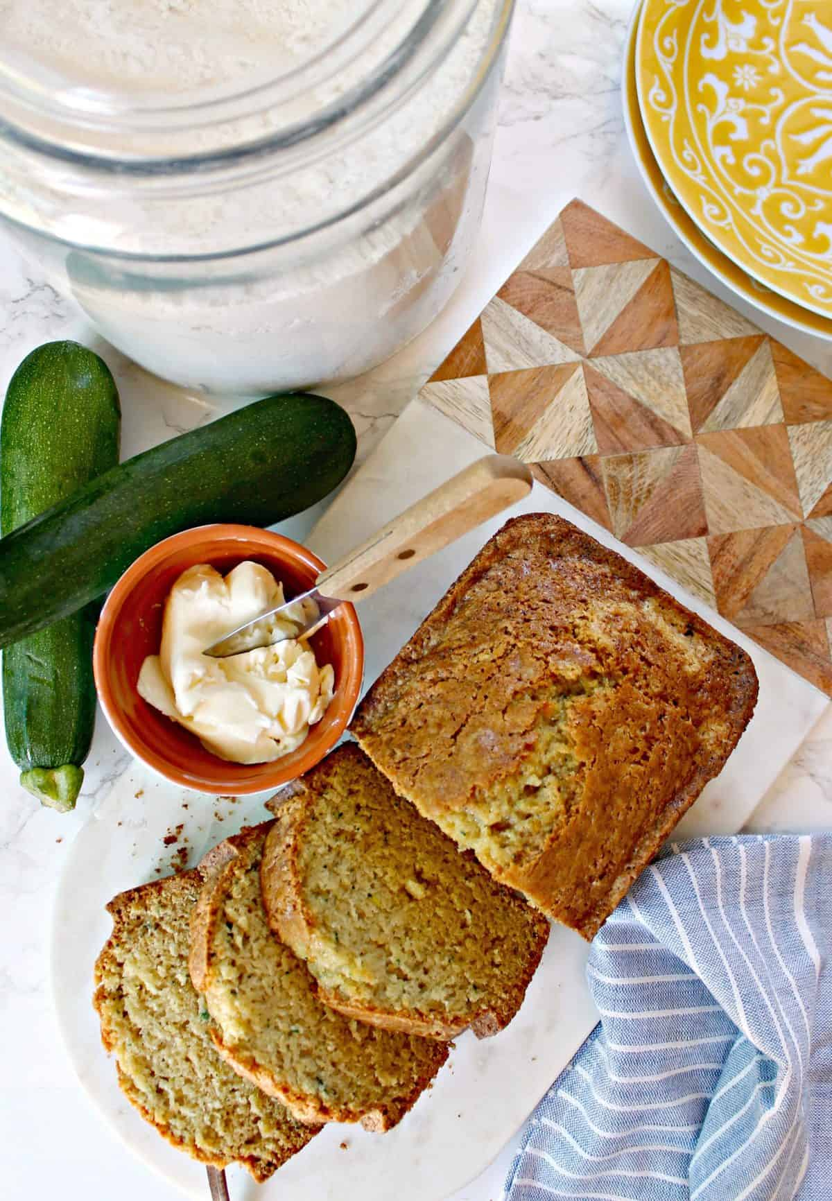 Overhead shot of sliced Zucchini Bread on a marble board with a blue linen napkin, small bowl of butter and whole zucchinis.