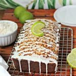 Close up of Banana-Coconut Bread with lime glaze on a cooling rack surrounded by a bowl of shredded coconut, sliced and whole limes and a kitchen towel.
