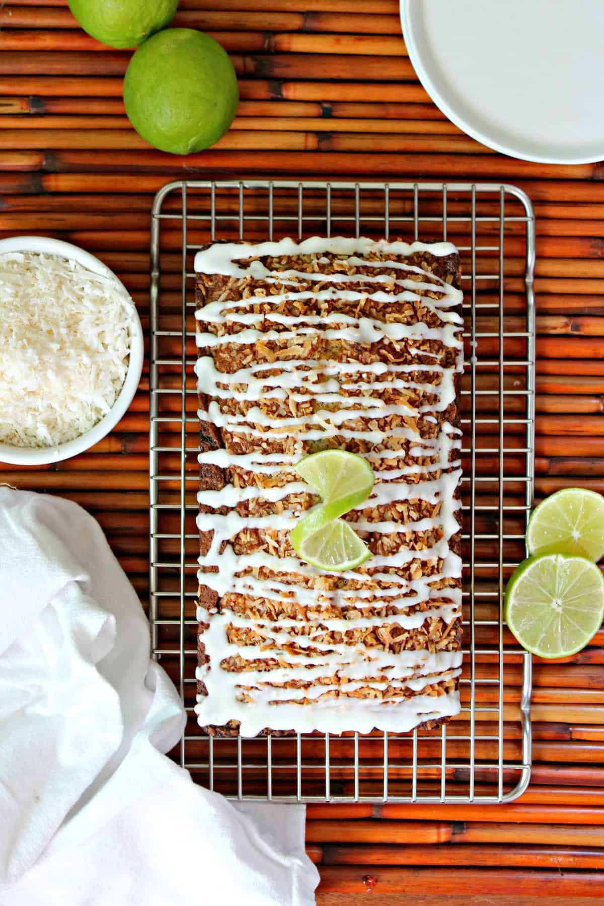 Overhead shot of Banana-Coconut Bread with lime glaze on a cooling rack surrounded by a bowl of shredded coconut, sliced and whole limes and a kitchen towel.