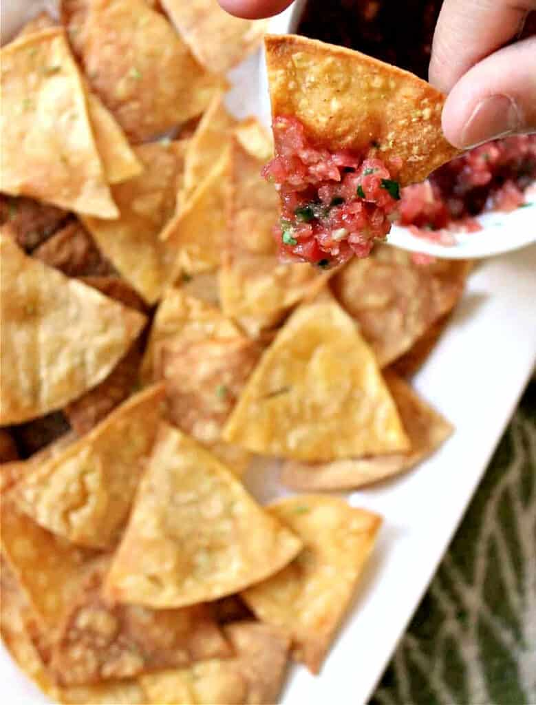 Hand holding a tortilla chip dipped in Grilled Watermelon Salsa with platter of tortilla chips in background.