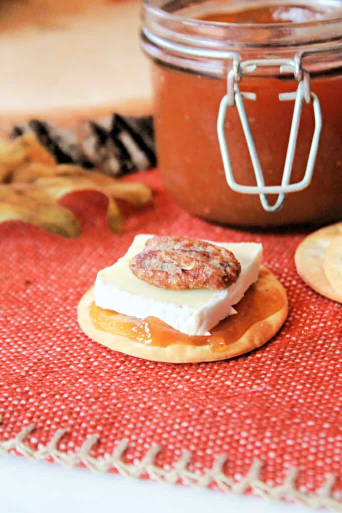 Caramel Pear Butter spread onto a cracker topped with a piece of brie and a candied pecan.