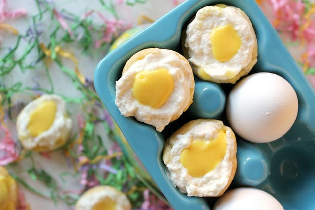 These tasty Easter cream puffs look like mini eggs with light whipped cream and a dollop of sweet vanilla glaze