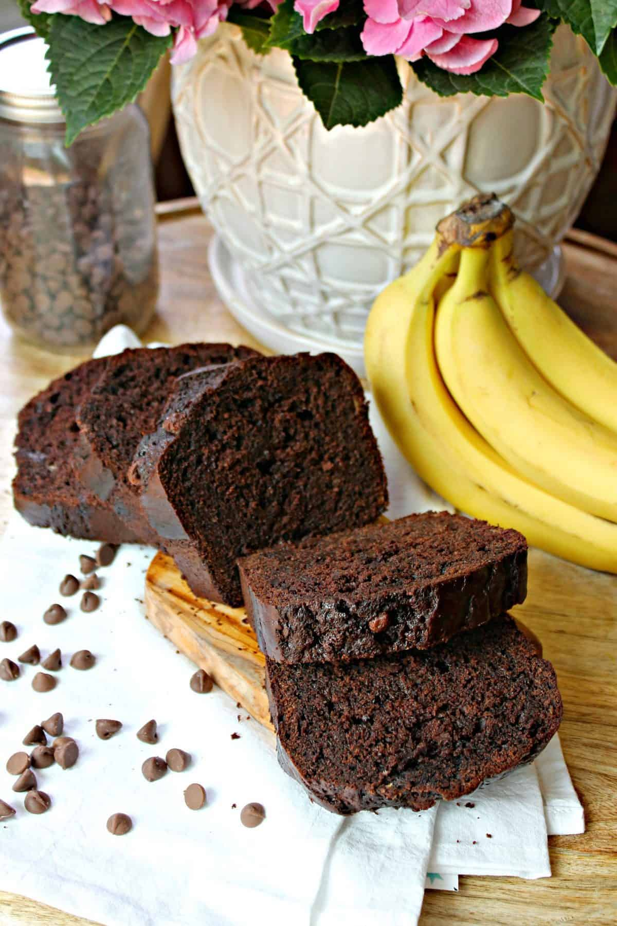 A sliced loaf of Double Chocolate Banana Bread on a wood cutting board surrounded by chocolate chips with bananas in the background.