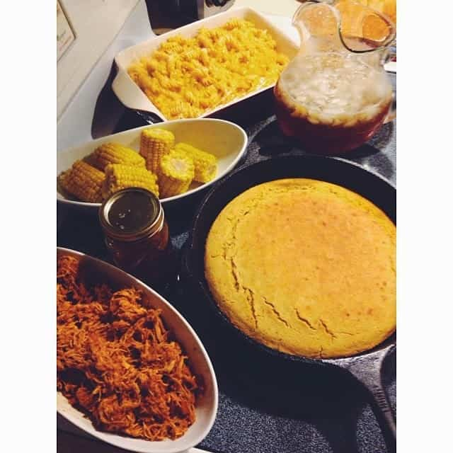 a southern style dinner spread with pulled pork, cornbread, corn on the cob, mac and cheese, and a pitcher of sweet tea