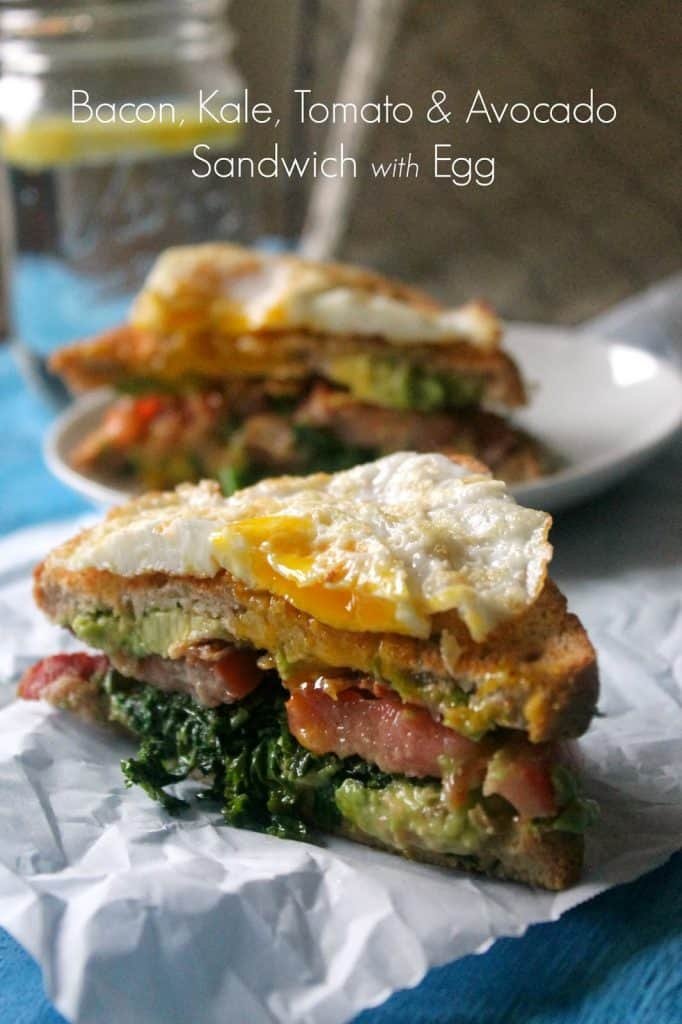 this bacon, kale, tomato and avocado sandwich is topped with an egg, making it a perfect brunch sandwich