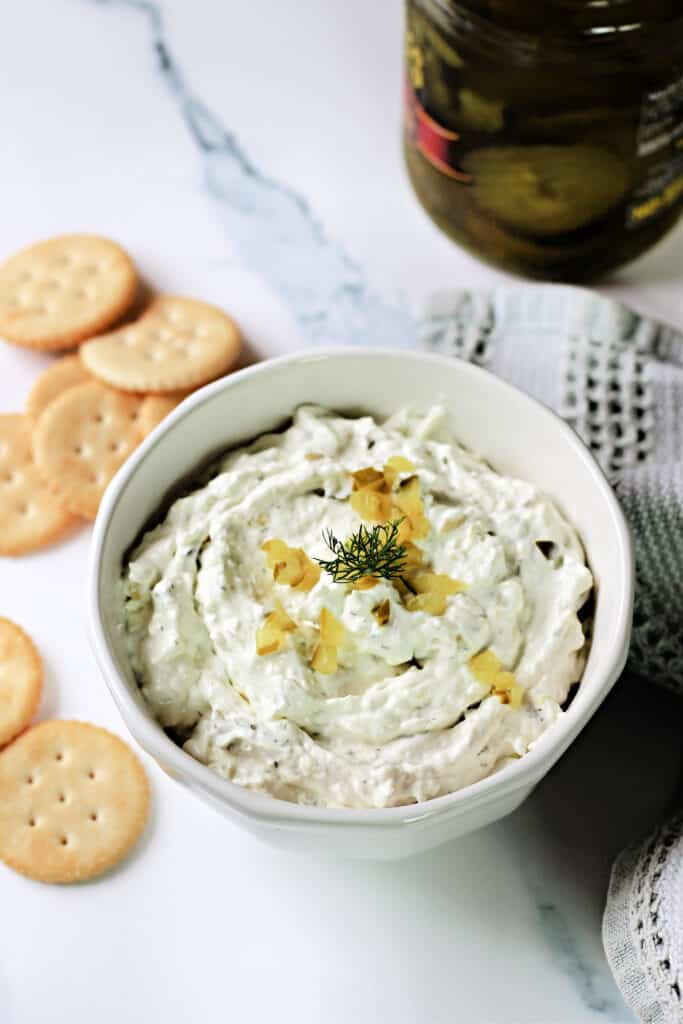 Dill Pickle Dip in a white bowl with crackers around it.