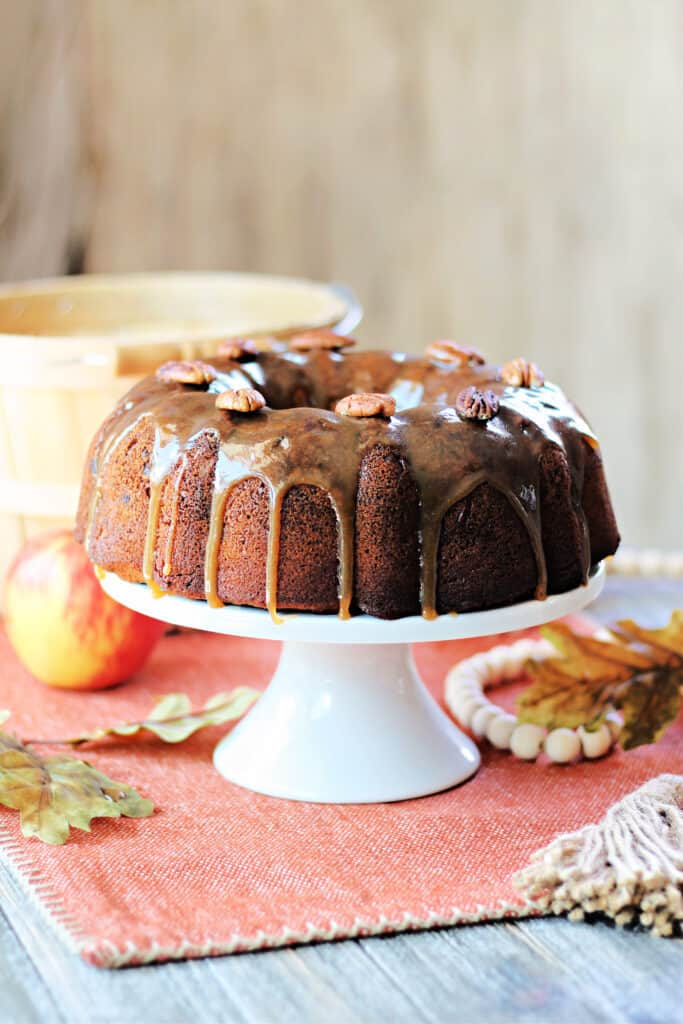 Honey Apple Bundt Cake on a white cake plate with fall leaves and apple in background.