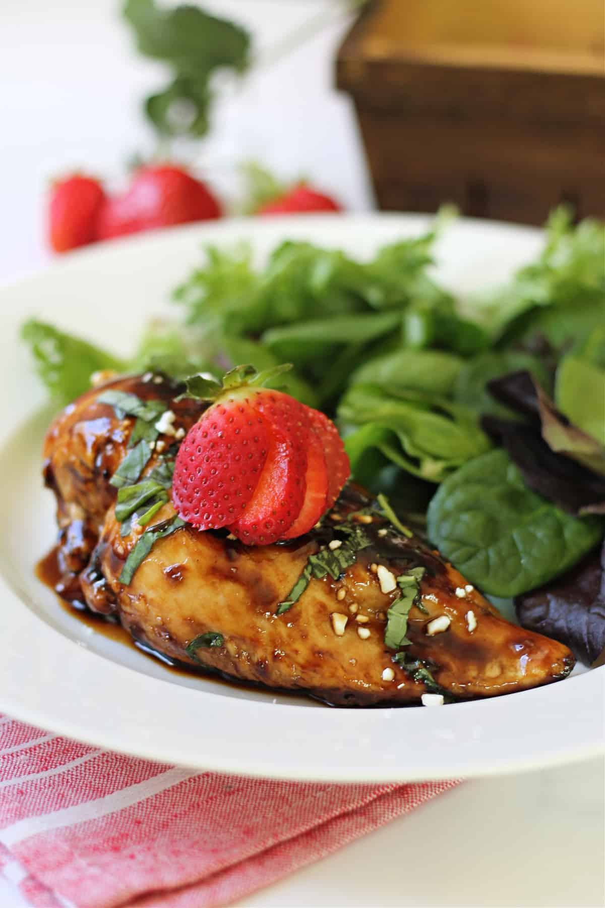 Close up of Strawberry Chicken on a white plate with a side salad.