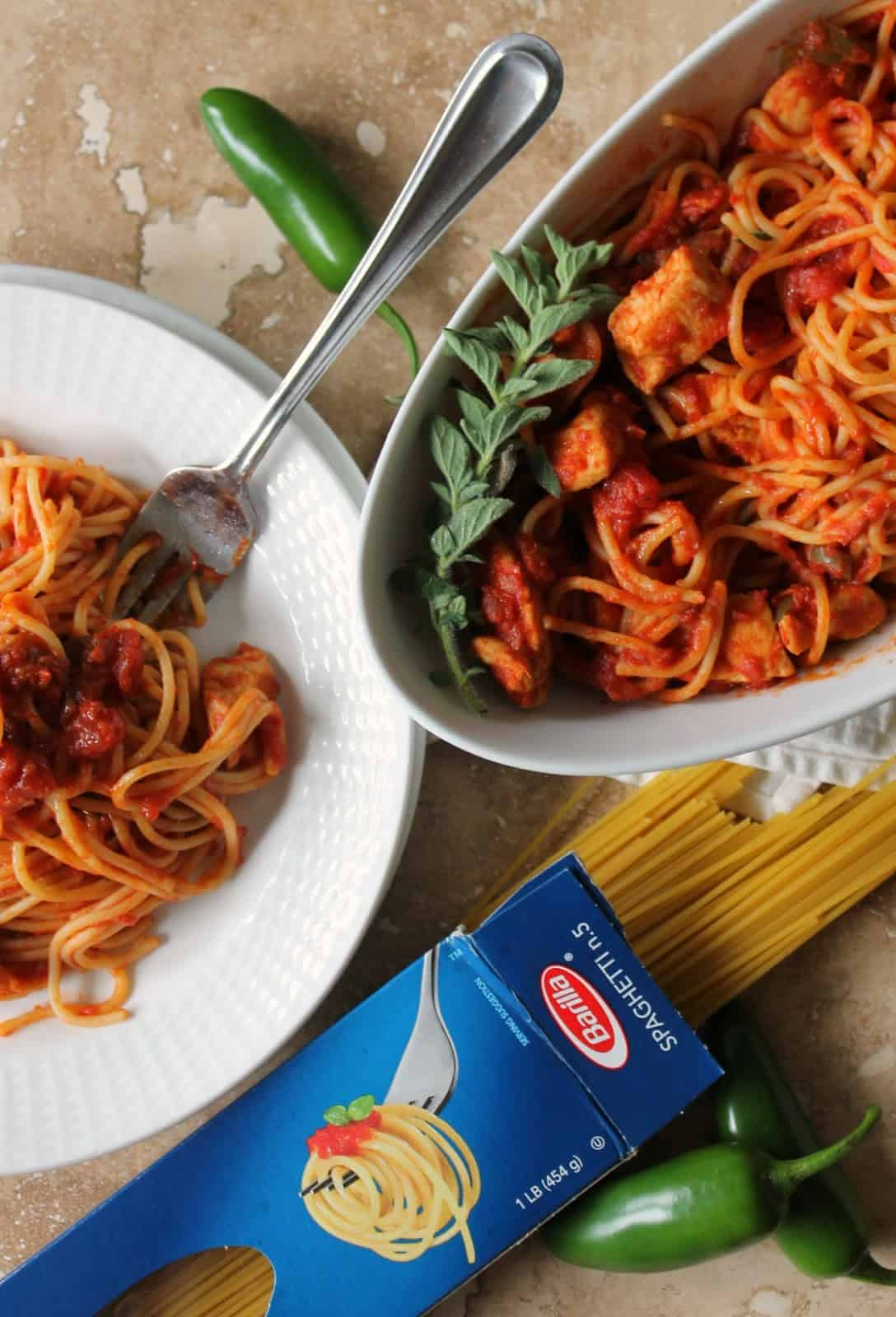 Overhead shot of Spaghetti with Chicken & Spicy Tomato Sauce on a dish and in serving dish with dry spaghetti noodles next to it.