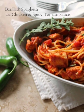 Close up of Spaghetti with Chicken & Spicy Tomato Sauce in an oval bowl with jalapeno peppers next to it.