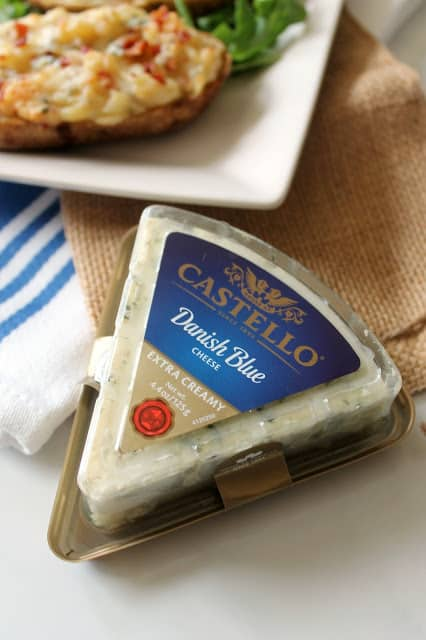 Castello Danish Blue Cheese in package with platter of twice baked potatoes behind it.