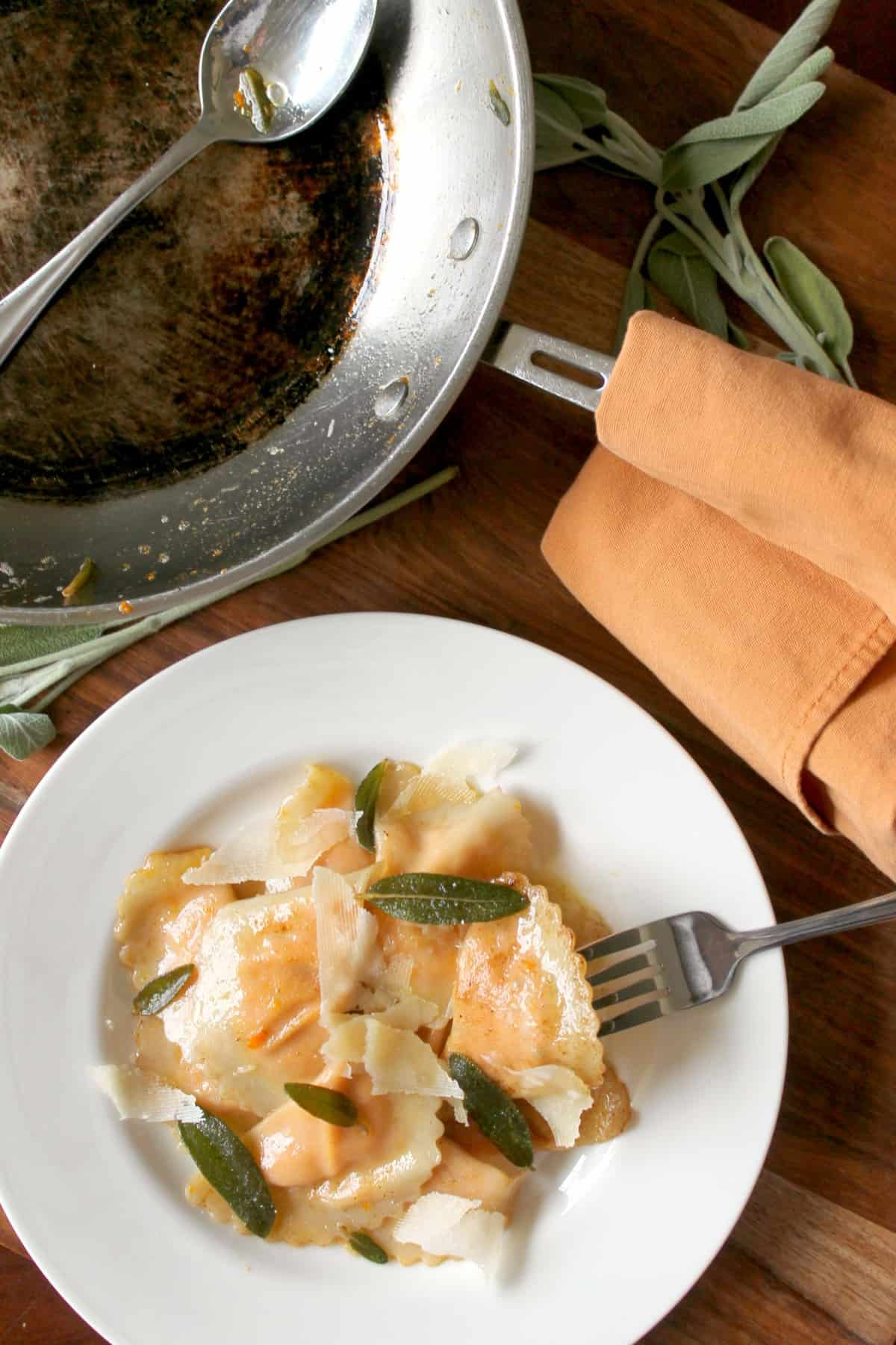 Roasted Carrot Agnolotti topped with shaved parmesan in a brown butter sage sauce