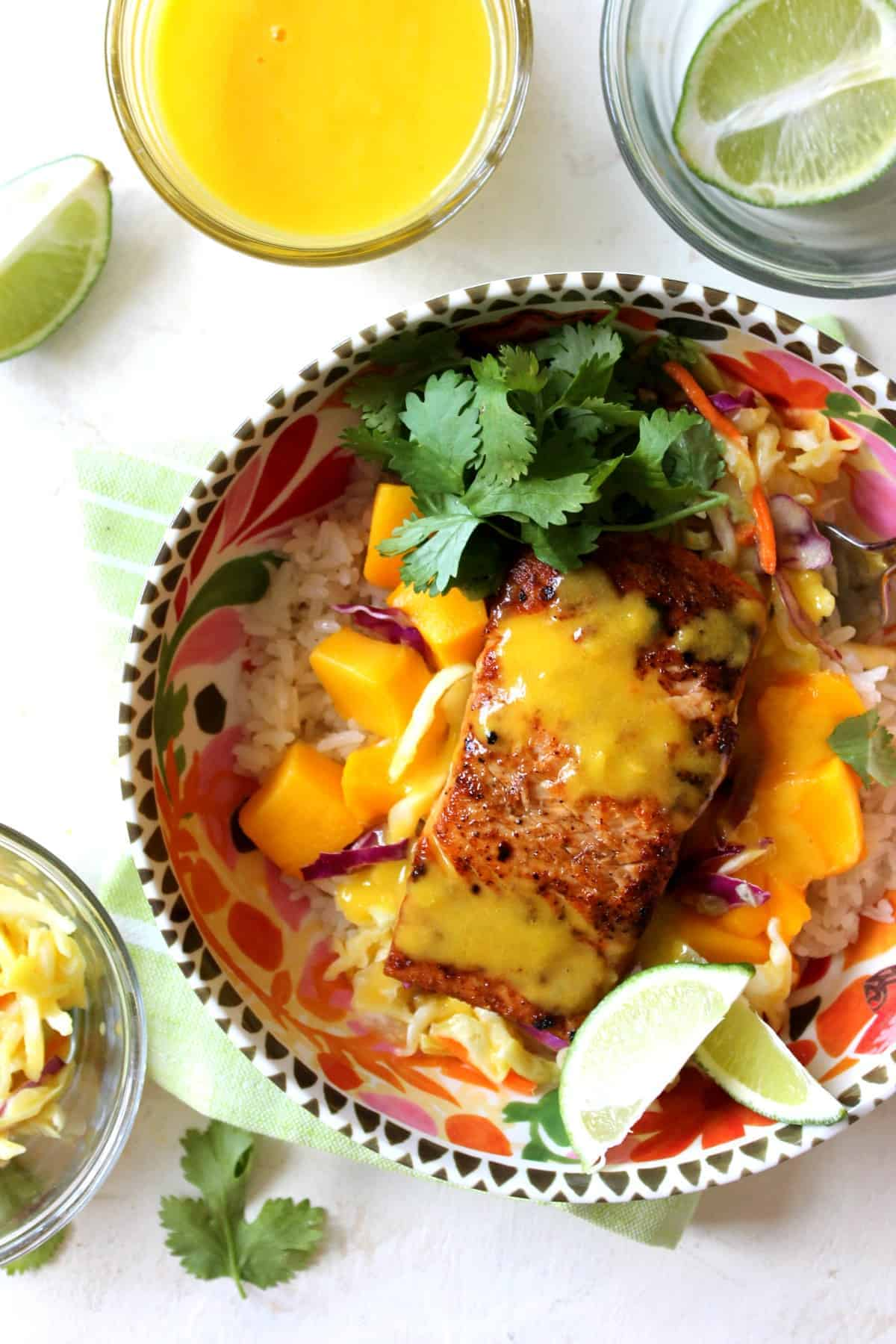 Tender mango salmon sits atop a bed of coconut rice with a sweet mango sauce