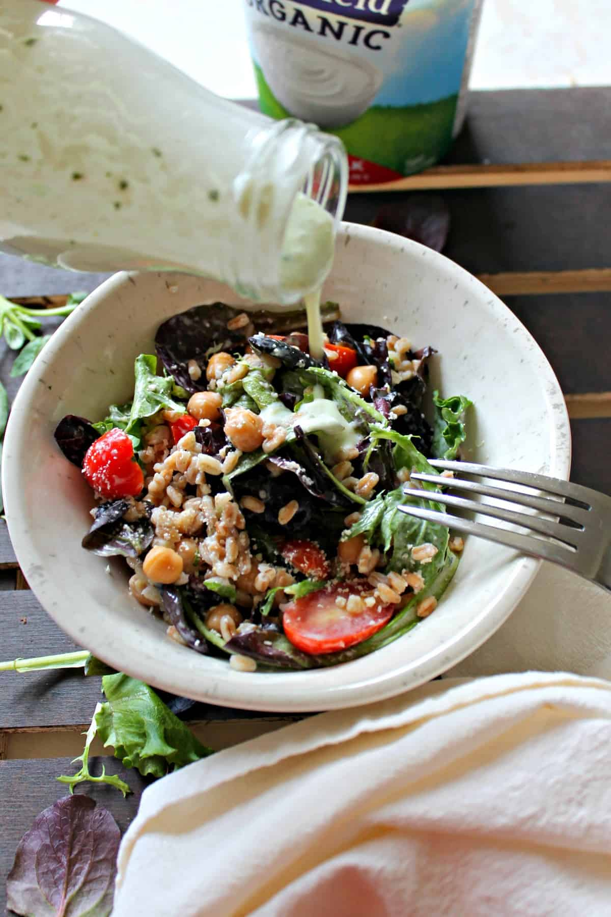 Farro & Mixed Greens Salad with Creamy Basil Parmesan Dressing is edible proof that salads don't have to be boring! Filled with satisfying ingredients like farro and chickpeas, and drizzled with a tangy yogurt-based dressing, this salad has staying power AND flavor!