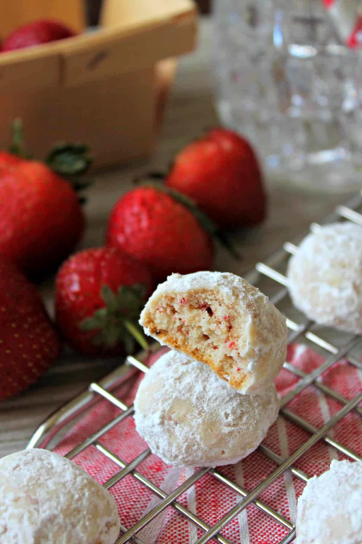Strawberry Meltaway Cookies! Crumbly and buttery like the classic version, this summery twist has the addition of pulverized freeze-dried strawberries giving them a hint of fruitiness. Finished off with a toss in powdered sugar, these easy-to-make cookies are a sweet summer treat you won't mind turning the oven on for!