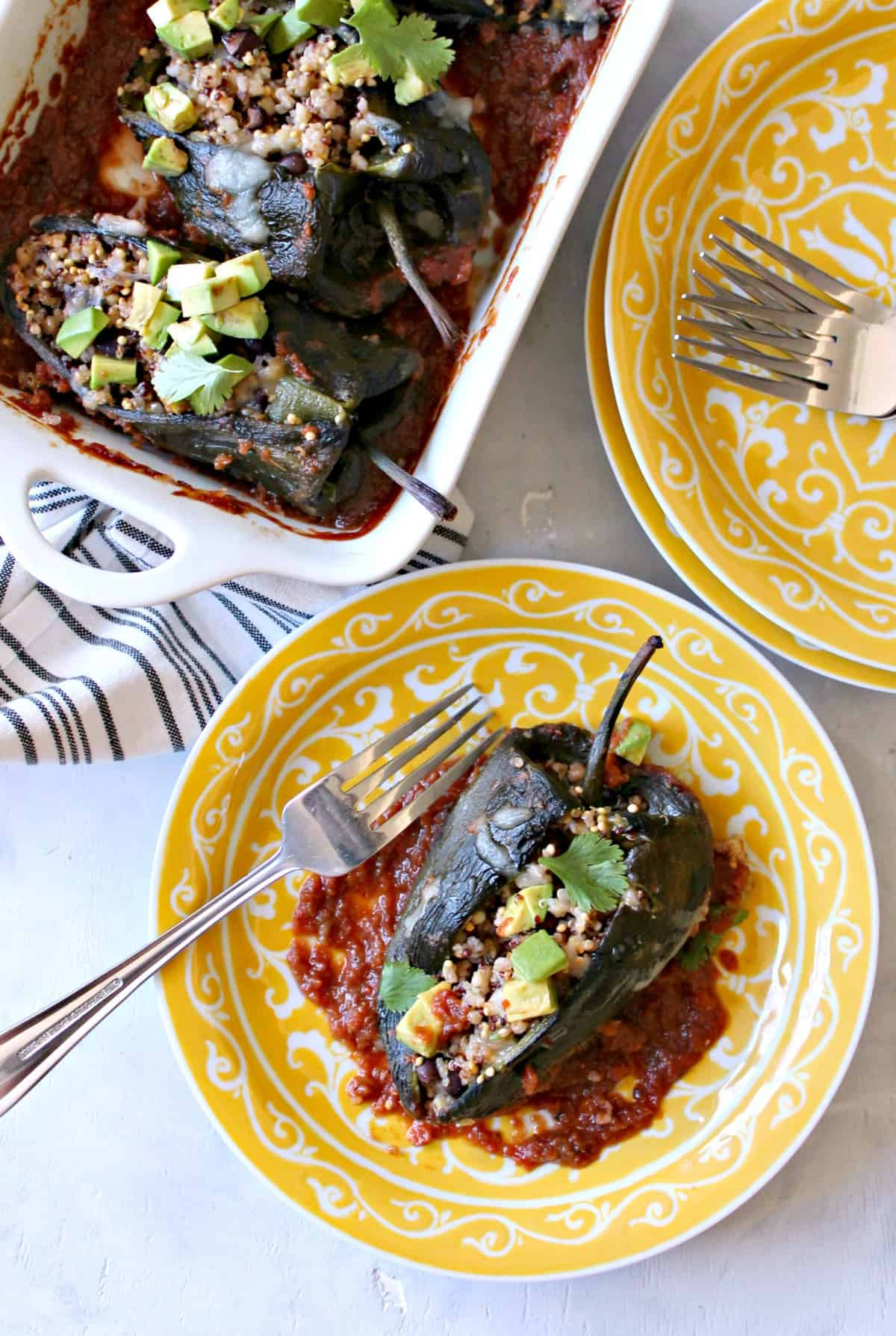 baked chili rellenos are poblano peppers stuffed with hearty grains, cheese, and baked in a spicy seasoned sauce