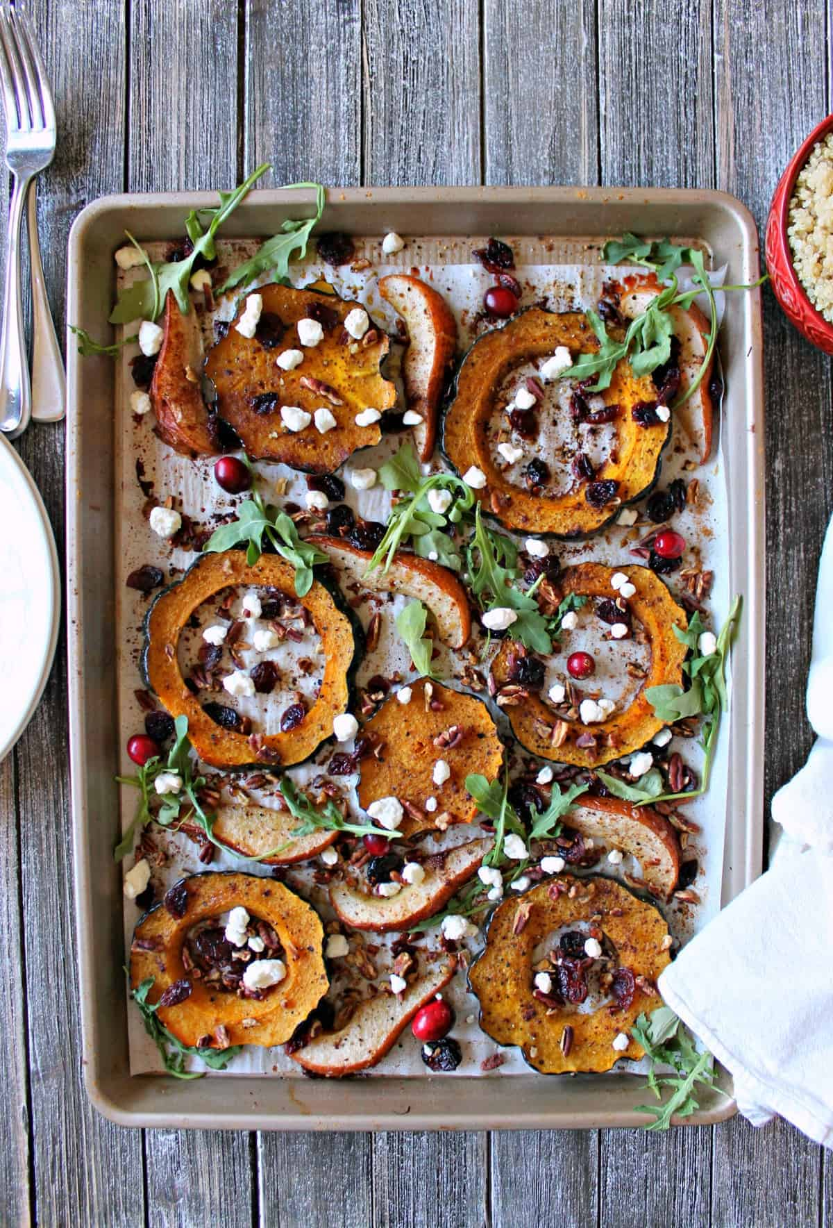 Spiced acorn squash, pears and quinoa cook simultaneously in the oven before being tossed with dried cranberries, pecans, goat cheese, and fresh arugula.