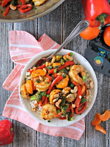 Tangerine Shrimp & Vegetable Stir Fry! Sweet red peppers, savory scallions and zesty tangerine add a burst of flavor to this easy shrimp stir fry dish. Serve over hot rice for a satisfying meal.