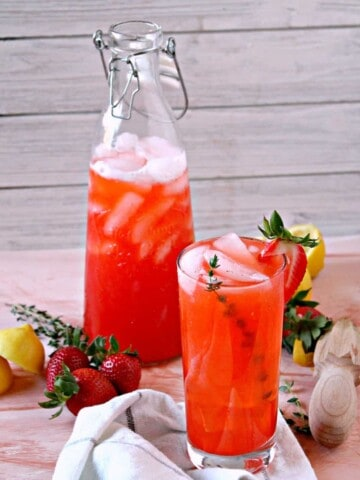 Strawberry thyme lemonade in a glass with carafe in the background.