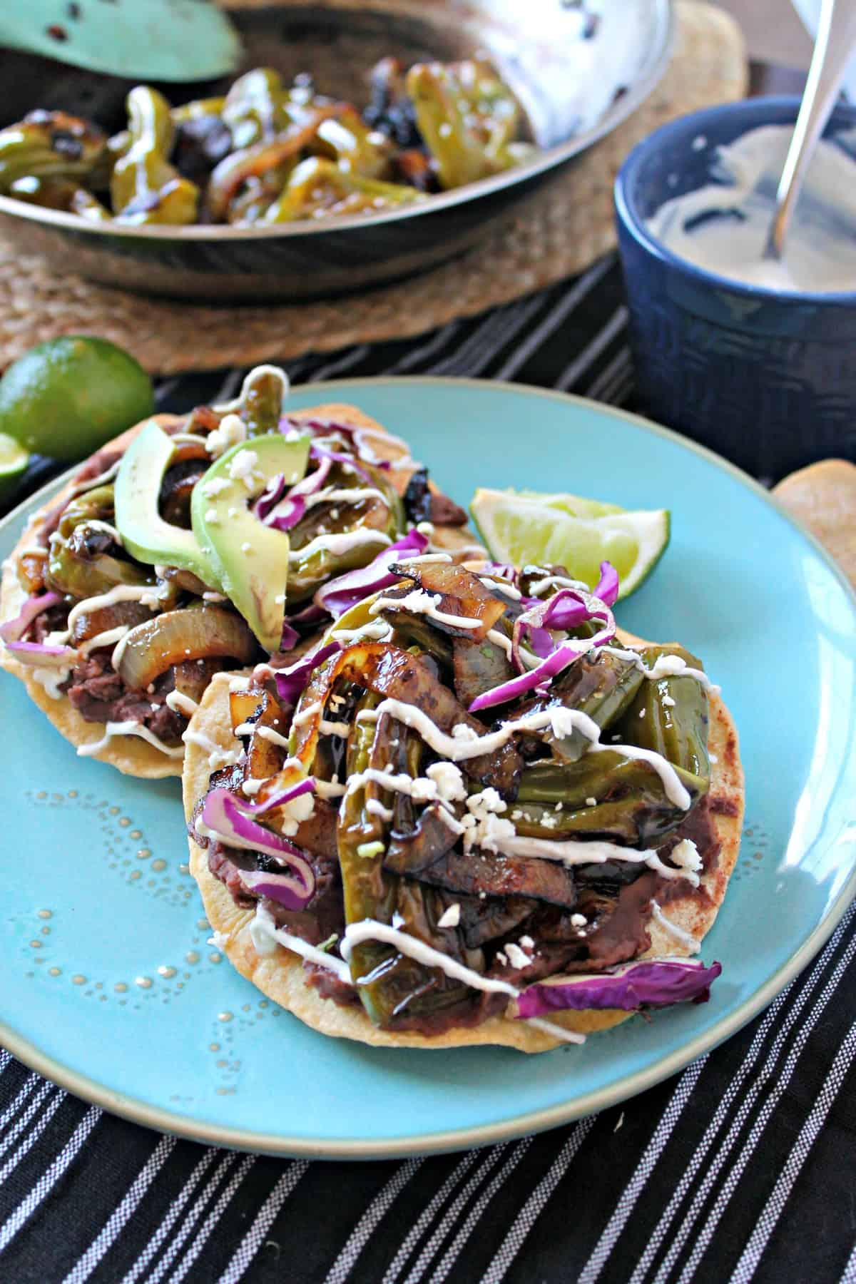 Charred Shishito Pepper & Refried Bean Tostadas! Just because these crunchy tostadas come together quickly doesn't mean they lack any flavor! Charred Shishito peppers, onions and refried beans drizzled with a Cumin & Lime Yogurt Sauce make a quick but delicious meal.