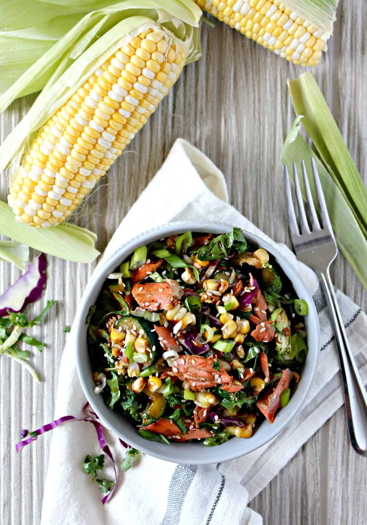 Asian-Inspired Grilled Salmon, Corn & Cucumber Salad! The fresh flavors of grilled summer corn and salmon pair perfectly with cool, crisp cucumber and crunchy slaw mix. A sweet and salty vinaigrette brings this satisfying salad together.