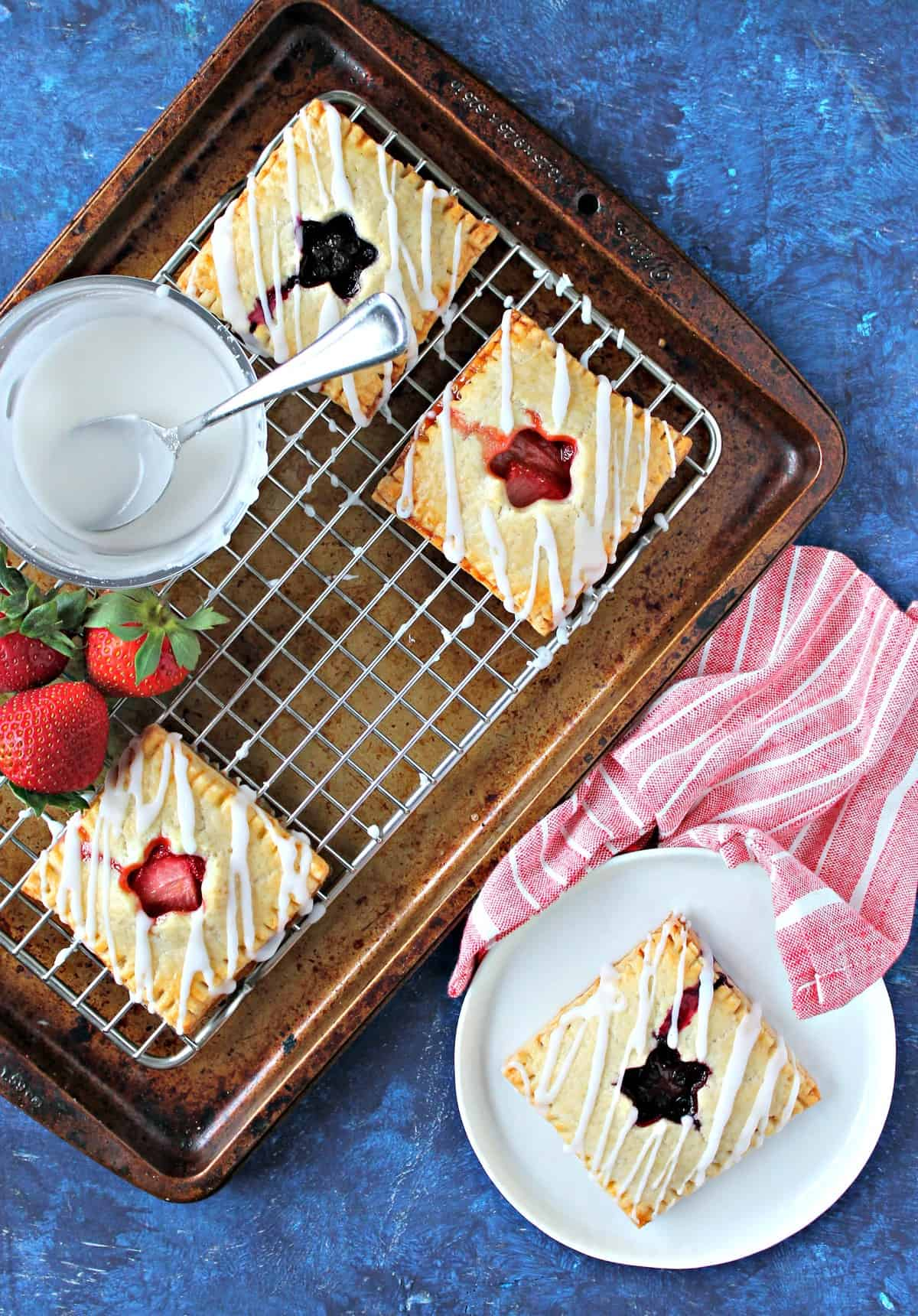 Patriotic Berry Hand Pies! These handheld, berry-filled beauties are the ultimate Memorial Day or 4th of July dessert with their red, white and blue details and star-spangled cutouts! They're easy to make and even easier to meet, making it ideal for casual celebrations and backyard barbecues.