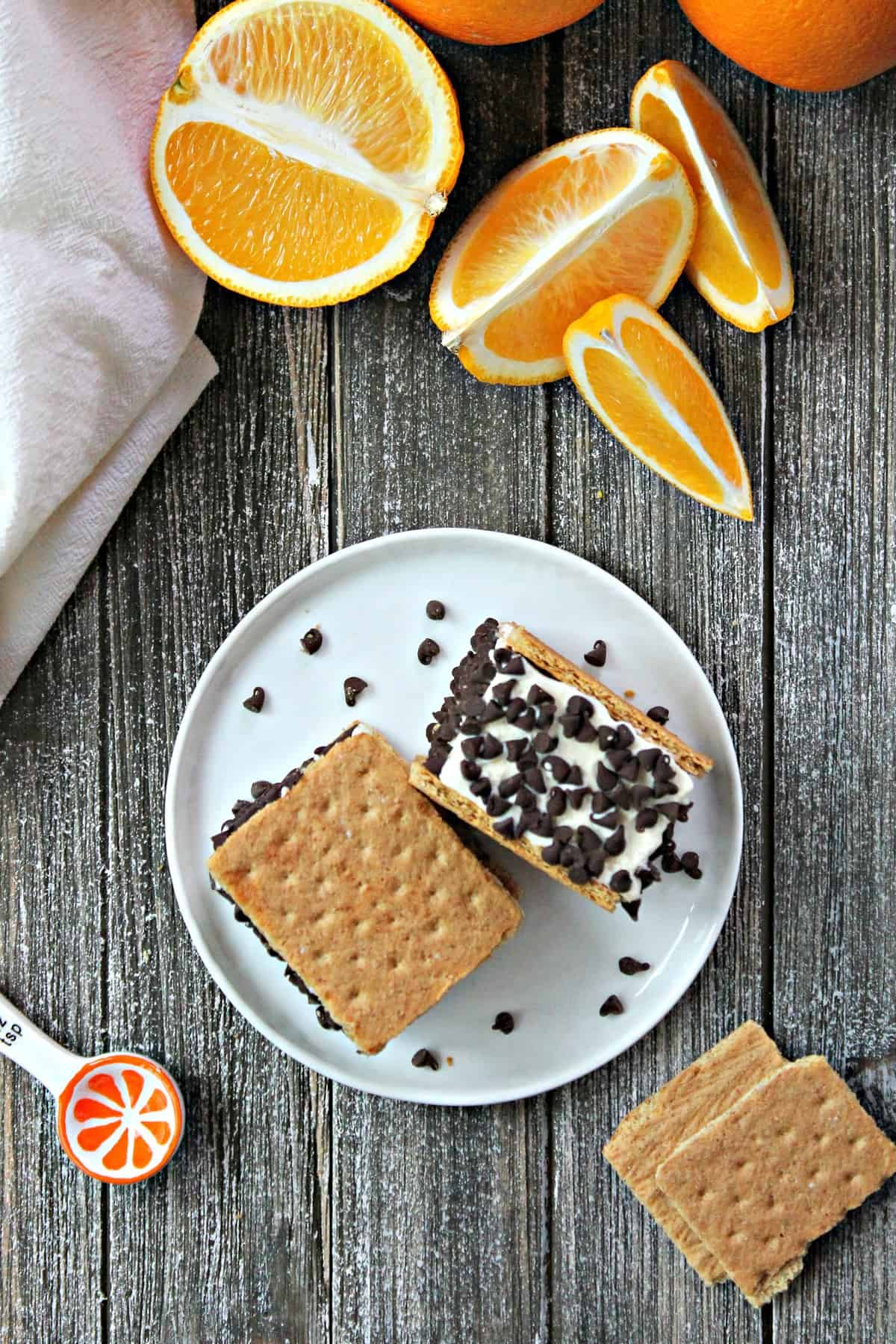 Easy No-Churn Orange-Chip Ice Cream Sandwiches! Orange-infused, no churn ice cream is cut into perfect portions, sandwiched between graham crackers & rolled in mini chocolate chips. A sweet summer dessert that's easy to whip up with your kids and even easier to eat!