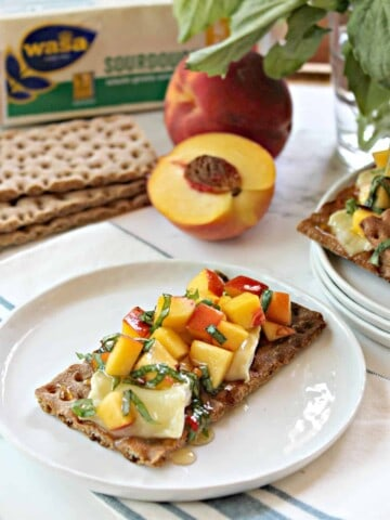 Hot Honey Peach & Brie Bruschetta! Ripe, diced peaches tossed with fresh basil, placed atop warm brie & drizzled with spicy honey on a hearty crispbread. The flavor of summer!