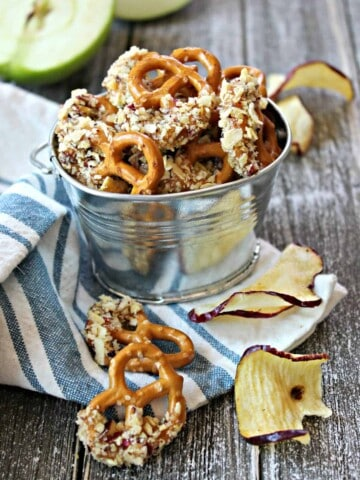 Caramel Apple Dipped Pretzel Bites! Crunchy mini pretzels dipped in sweet caramel and rolled in crushed apple chips will be the highlight of your fall dessert table! These irresistible, easy-to-make bites make fantastic game day snacks for tailgates and fall parties; they also make a great treat to package and gift for any autumn occasion.
