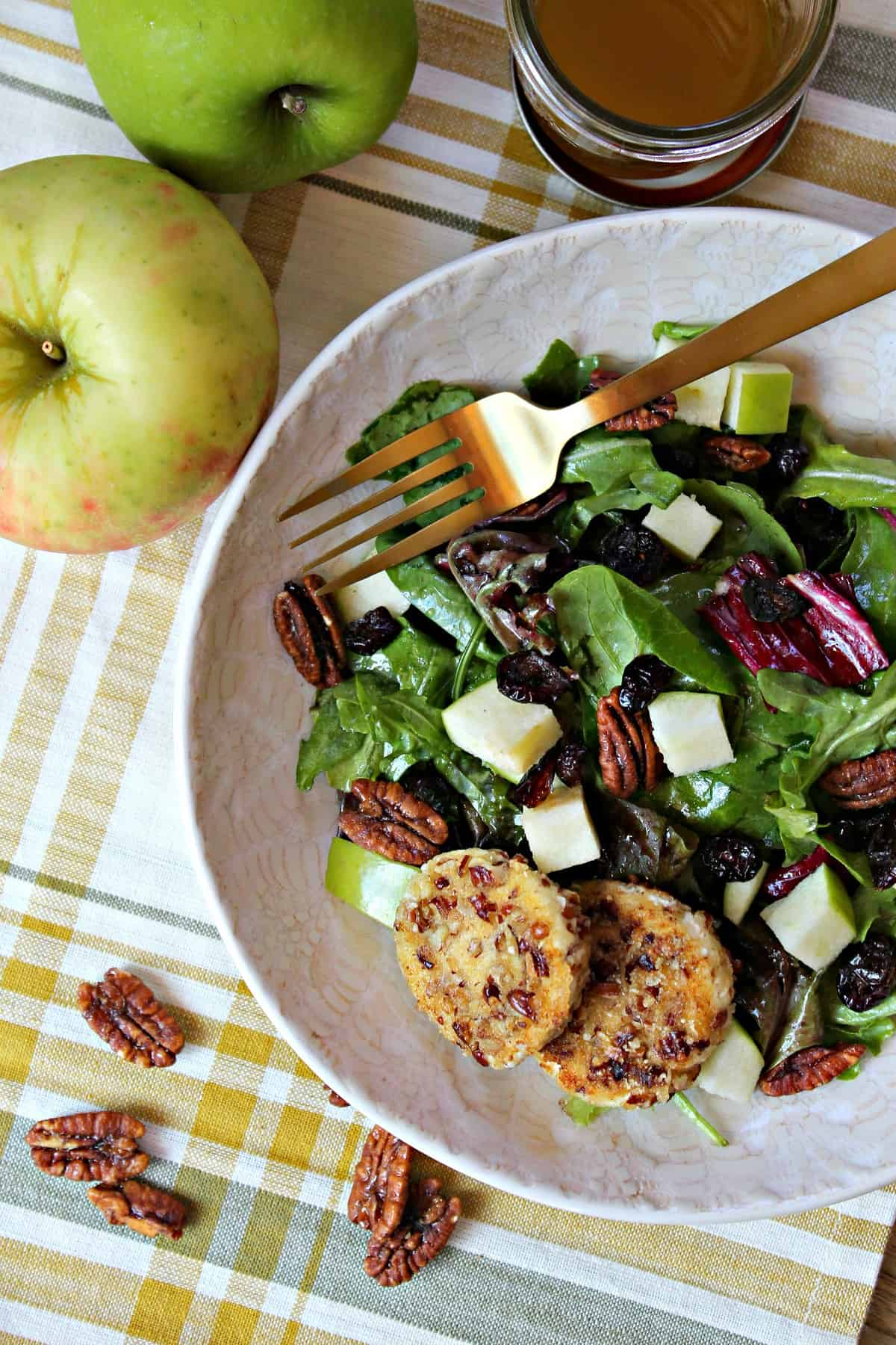 Crisp apples, cranberries, and pecan-crusted goat cheese medallions top this fresh autumn harvest salad for a sweet and filling lunch