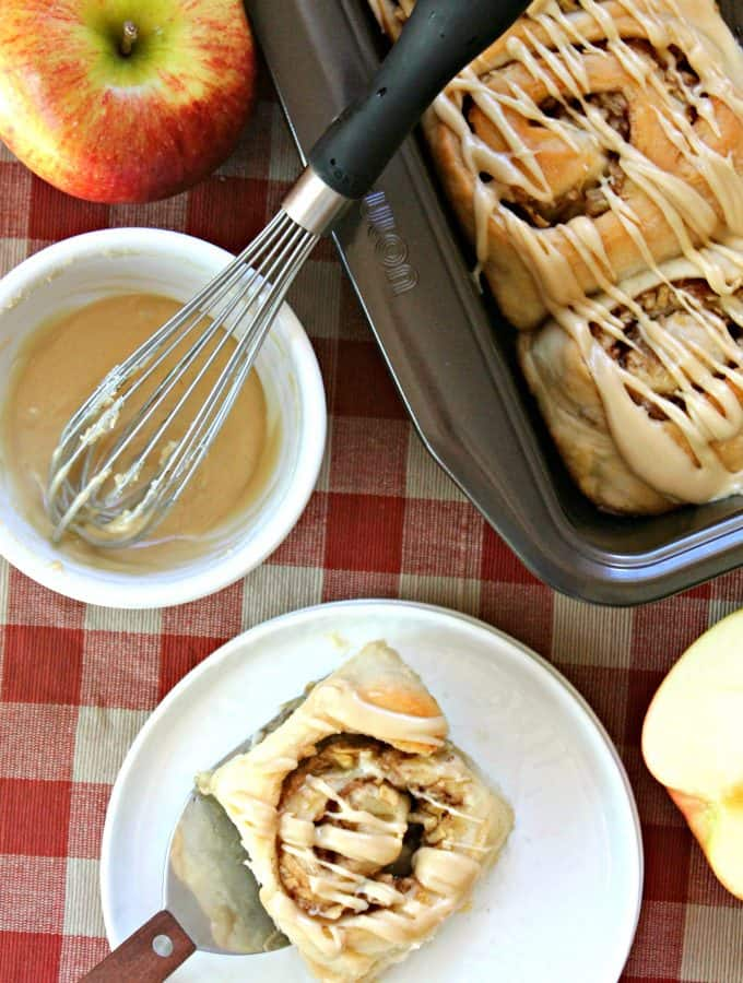 Easy Caramel Apple Cinnamon Rolls! Tender, store-bought bread dough nestles heaps of sweet shredded apples, brown sugar and cinnamon. Topped off with a gooey caramel icing, these rolls are the ultimate holiday treat!