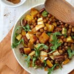 "Pumpkin-Spiced Roasted Squash & Chickpea Salad! Need something a little different to serve alongside your holiday staples? This warm salad dish is sweet, savory and filled with the flavors and aromas of the holiday season!  Delicata squash is having a moment. I noticed its popularity on the rise last fall, and I've continued to see more and more people using it lately. I never jumped on the bandwagon last year, but when I started seeing them piled into pretty mounds at Trader Joe's at the start of autumn this year, I figured it couldn't hurt to toss a few in my cart and experiment with them at home. Now that I've cooked with them several times, I don't know why it took me so long to get on board! If you like squash but dread dealing with prepping it, then Delicata is the perfect variety for you. Unlike its tough-skinned counterparts, there is no need to peel Delicata squash which makes it a huge time saver. Since it's typically smaller than butternut squash and not quite as wide as an acorn squash, it's also much easier to chop, which I deeply appreciate since I can't tell you how many times I've feared for my digits. {This is also the reason butternut squash is one of the only vegetables I buy pre-chopped -- unharmed fingers are totally worth the convenience charge, if you ask me.} Anyway, I bought some Delicata squash a few weeks ago to serve as a side dish when I had my family over for dinner, and everyone raved about how I prepared it so much that I decided I'd work on a Thanksgiving-worthy recipe to share here using the gourd-du-jour. This Pumpkin-Spiced Delicata Squash & Chickpea Salad is what I came up with! I know I throw this phrase around a lot, but it is SO EASY to make, especially since that Delicata squash is so much less difficult than the other kinds. You just chop, drop and toss everything with a mixture of oil, maple syrup and seasoning {salt and pumpkin spice blend to be exact} on one sheet pan, and let the oven do the rest of the work. The maple syrup glazes both the squash and the chickpeas, caramelizing everything as it roasts, and makes them taste like candy. The pumpkin spice pairs like a a dream with the naturally sweet and creamy interior of the squash. Ugh. It's so good. If you want to simplify the prepping even further, you don't need to chop the squash into cubes if you don't want to -- it's fairly quick-cooking even when it's sliced in larger pieces. I thought the cubes worked well with the size of the chickpeas to make it easily ""poppable"", but you can chop it however you'd like. Finish it off by tossing in some pecans or pumpkin seeds, and maybe a handful of chopped greens for color and freshness, and you've got a new side dish for you Thanksgiving table that will be joining Delicata squash in the highest rankings of supermarket superlatives, taking the ""Most Requested Side Dish"" category every year. ;)"