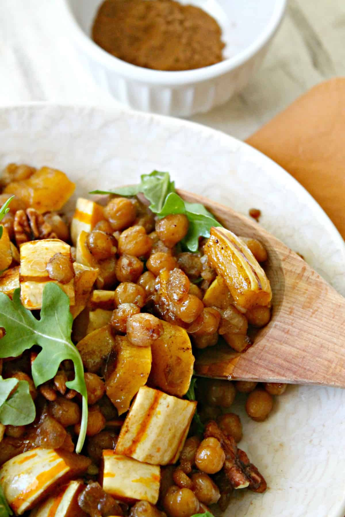 Pumpkin-Spiced Roasted Squash & Chickpea Salad! Need something a little different to serve alongside your holiday staples? This warm salad dish is sweet, savory and filled with the flavors and aromas of the holiday season! Delicata squash is having a moment. I noticed its popularity on the rise last fall, and I've continued to see more and more people using it lately. I never jumped on the bandwagon last year, but when I started seeing them piled into pretty mounds at Trader Joe's at the start of autumn this year, I figured it couldn't hurt to toss a few in my cart and experiment with them at home. Now that I've cooked with them several times, I don't know why it took me so long to get on board! If you like squash but dread dealing with prepping it, then Delicata is the perfect variety for you. Unlike its tough-skinned counterparts, there is no need to peel Delicata squash which makes it a huge time saver. Since it's typically smaller than butternut squash and not quite as wide as an acorn squash, it's also much easier to chop, which I deeply appreciate since I can't tell you how many times I've feared for my digits. {This is also the reason butternut squash is one of the only vegetables I buy pre-chopped -- unharmed fingers are totally worth the convenience charge, if you ask me.} Anyway, I bought some Delicata squash a few weeks ago to serve as a side dish when I had my family over for dinner, and everyone raved about how I prepared it so much that I decided I'd work on a Thanksgiving-worthy recipe to share here using the gourd-du-jour. This Pumpkin-Spiced Delicata Squash & Chickpea Salad is what I came up with! I know I throw this phrase around a lot, but it is SO EASY to make, especially since that Delicata squash is so much less difficult than the other kinds. You just chop, drop and toss everything with a mixture of oil, maple syrup and seasoning {salt and pumpkin spice blend to be exact} on one sheet pan, and let the oven do the rest of the work. The maple sy