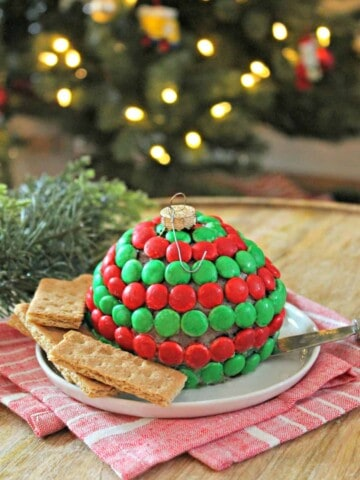 """Mint Cookies & Cream Dessert Cheese Ball! Crushed creme-filled chocolate cookies stud a sweet and creamy cheesecake """"ornament"""". A hint of mint gives it a holiday twist! This last minute holiday dessert couldn't get any easier or cuter! Serve with fruit or cookies for a festive treat."""