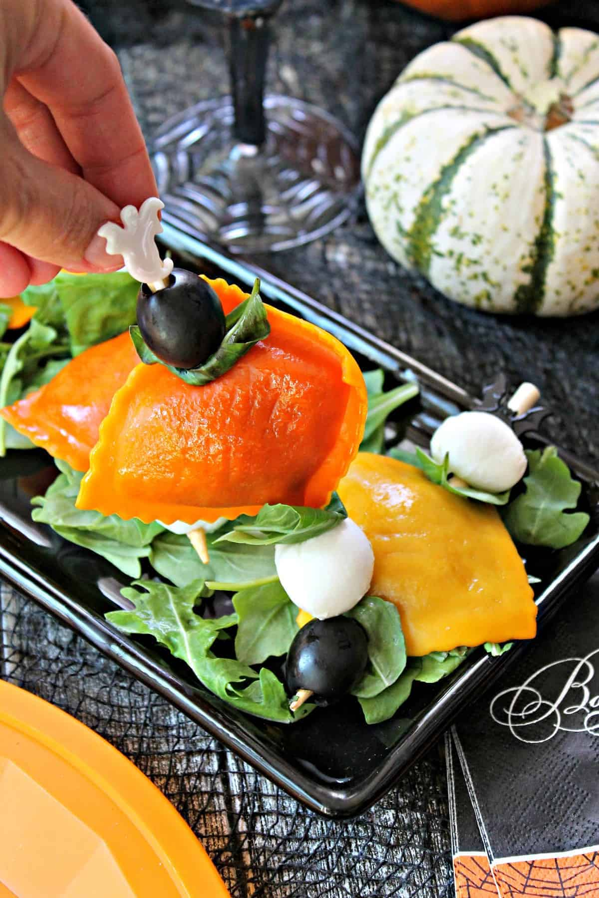 Orange and yellow pumpkin ravioli threaded onto bamboo skewers with mozzarella balls, black olives and fresh basil on a Halloween background.
