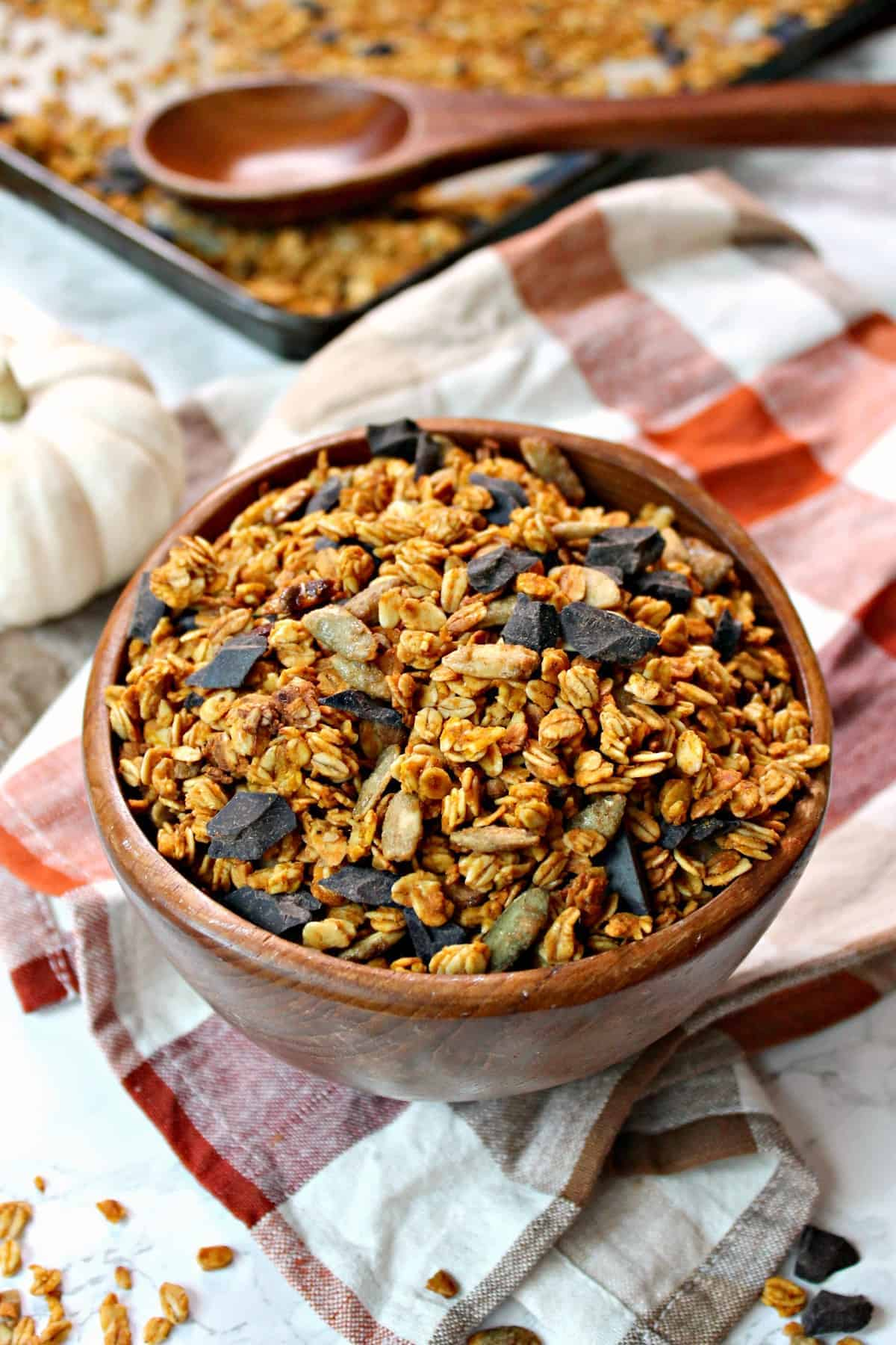 Pumpkin Seed Chocolate Chunk Granola! This crunchy and addictive homemade granola gets a triple dose of pumpkin-y goodness thanks to the addition of pumpkin spiced pumpkin seeds, pumpkin pie spice and pumpkin puree. Semi-sweet chocolate chunks add decadence to this heavenly fall concoction!