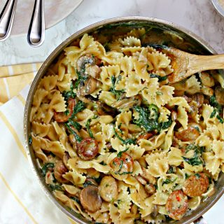 A large skillet filled with Creamy Mushroom & Chicken Sausage Florentine Pasta with a yellow and white striped dish towel underneath.