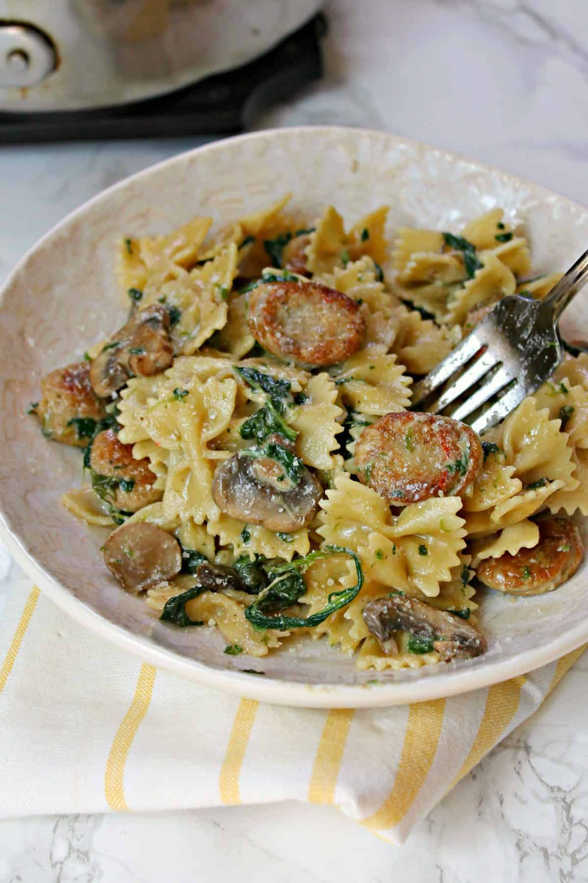 Close up of Creamy Mushroom & Chicken Sausage Florentine Pasta with a fork.