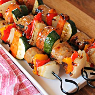 Close up of Glazed Chicken Apple Sausage & Sweet Potato Kabobs on a white platter.